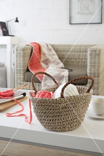 Strickbandknäuel in rustikaler Häkeltasche auf weißem Tisch