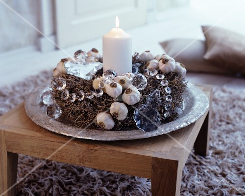 Rustic Advent wreath made from natural materials and lit white candle on exotic-wood table