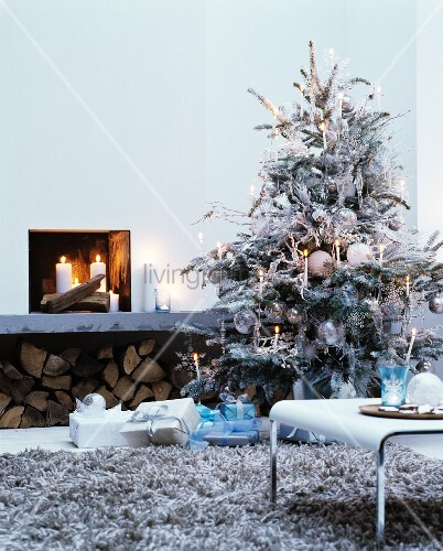 Christmas tree sprayed white and decorated with white candles and glass baubles next to open fire
