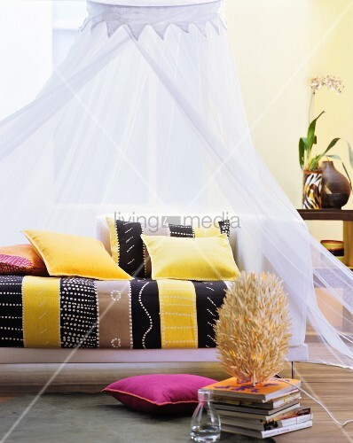 Sofa im Ethnolook mit bunten Kissen und Baldachin