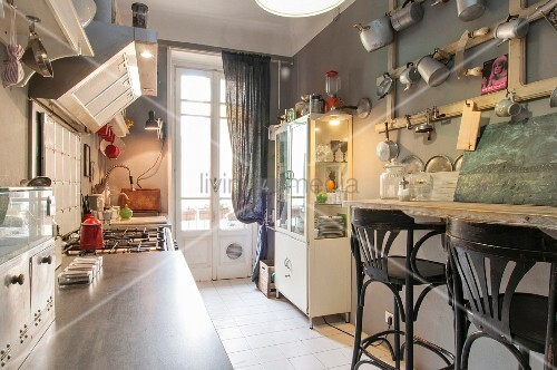 Breakfast bar, enamel tinware hung on wall and display case in vintage-style kitchen