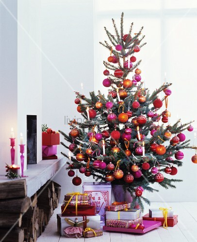 Presents below Christmas tree lavishly decorated with pink, red and orange baubles