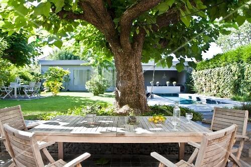 sitzplatz im garten unter einem baum blick auf pool und bungalow bild kaufen living4media. Black Bedroom Furniture Sets. Home Design Ideas