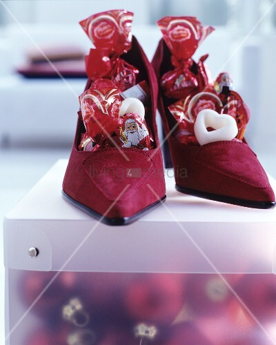 Dark red suede ladies' shoes filled with Chocolate Father Christmases and sweets