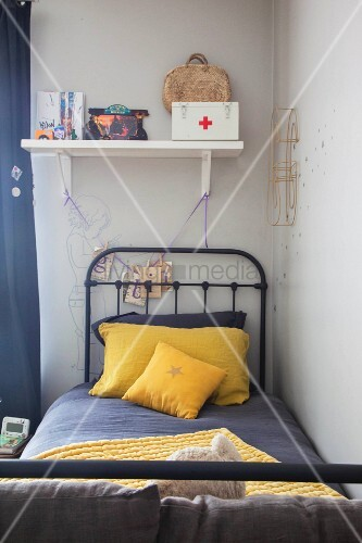 Grey and yellow bed linen on metal bed in child's bedroom