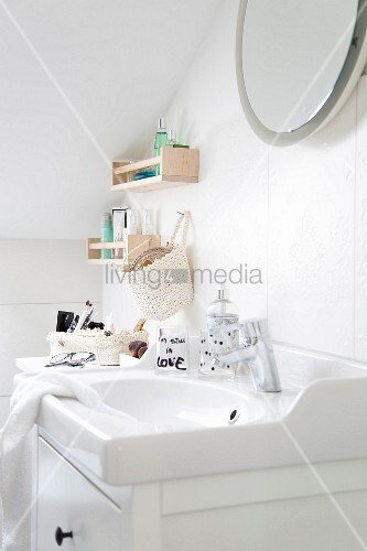 Washstand with white base unit below sloping ceiling and shelves and basket mounted on wall
