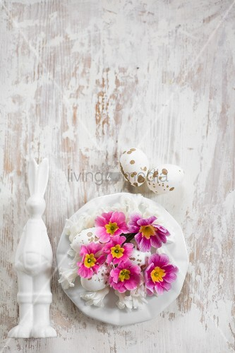 Easter bunny next to plate of flowers and speckled eggs
