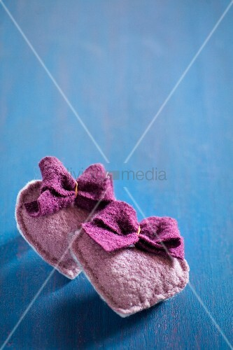 Hand-sewn felt hearts with bows on blue surface