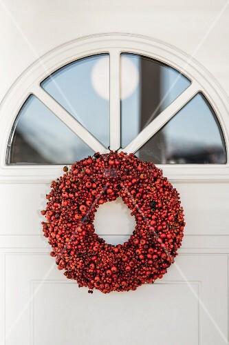 Wreath of red berries below fanlight in front door