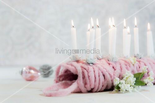 Kleine brennende Kerzen auf einem rosa Knäuel Wolle