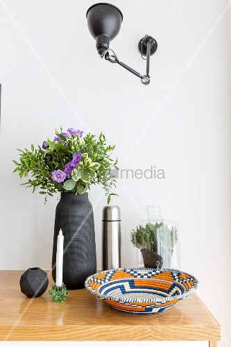 Anglepoise lamp mounted on wall above ornaments