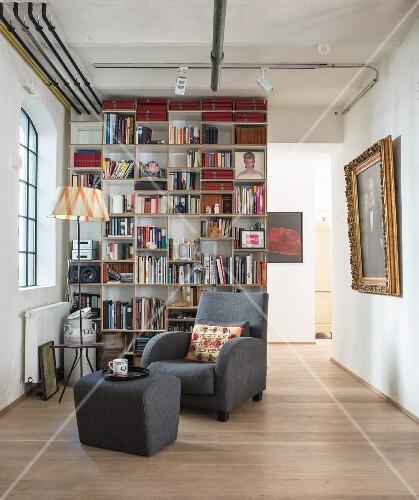 Leseecke mit grauem Sessel und Fußhocker vor Bücherregal