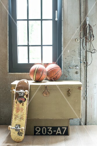 Skateboard and basketballs on old trunk below industrial window