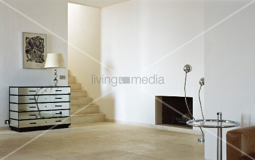 Minimalist living room with designer mirrored chest of drawers beside an open hallway with stairs and side table in Bauhaus style