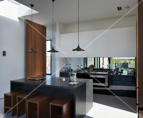 Kitchen unit with view of landscape and cubic dining furniture with wooden stools beneath sunny skylight in South American designer kitchen-dining room