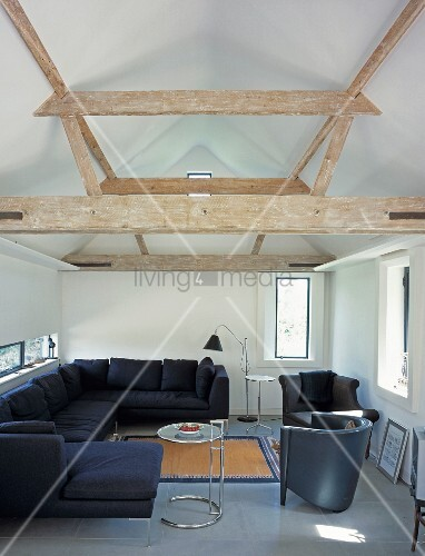 Black living room suite with side tables in Bauhaus style under rustic wood beam construction