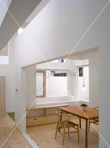 Simple wooden chair and table in Bauhaus style in a modern house with cut outs in the wall