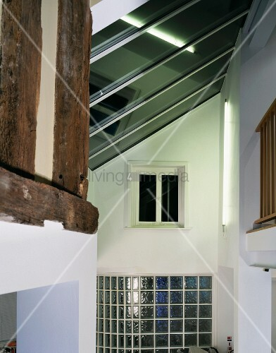Multi-storey open lobby with skylight and glass brick wall