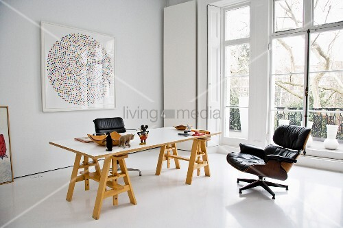 A desk on wooden trestles and a Baushaus-style armchair in an elegant, minimalistic room