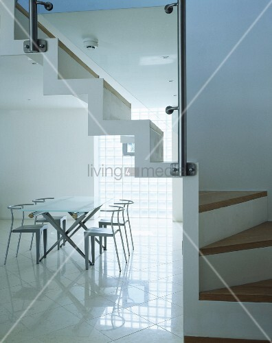 Minimalist dining room with table and designer chairs on a reflective tiled floor and open stairway