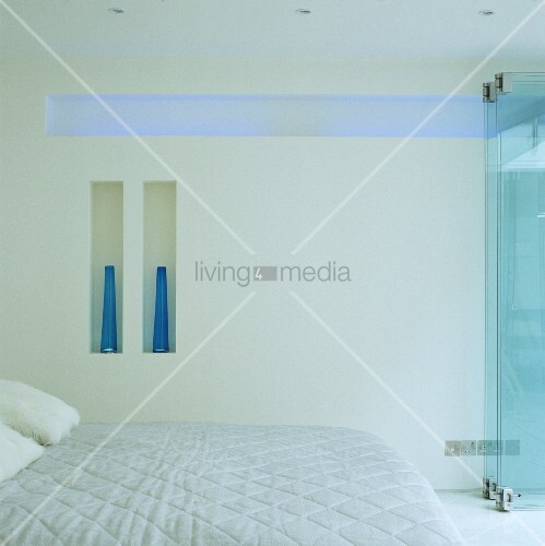 White bedroom with double bed and indirect blue lighting in a horizontal wall niche