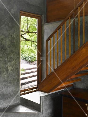 schwebende holztreppe und podest vor offener haust r im kleinen vorraum aus beton bild kaufen. Black Bedroom Furniture Sets. Home Design Ideas