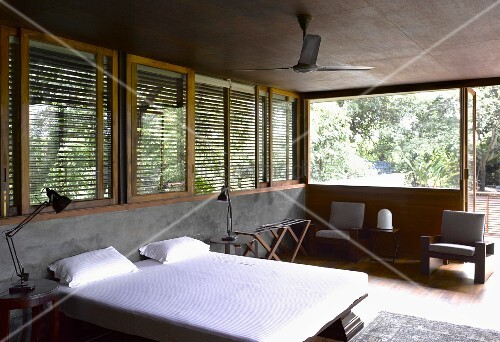 Double bed with white bed linen in front of half-height concrete wall and wooden blinds on windows