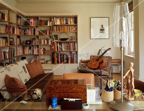 Jugendliches Wohnzimmer in Naturfarben mit Bücherwänden, Gitarre und ...