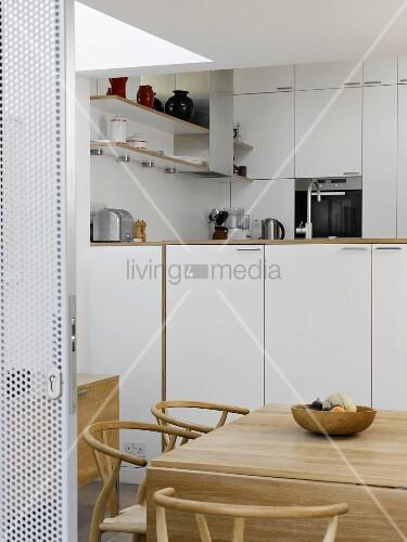 offene schiebet r aus lochmetall und blick in k che mit klassikerst hlen am essplatz bild. Black Bedroom Furniture Sets. Home Design Ideas