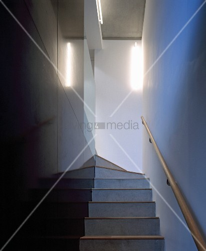 Narrow Staircase With Black Stone Tiled Wall And Wooden Handrail