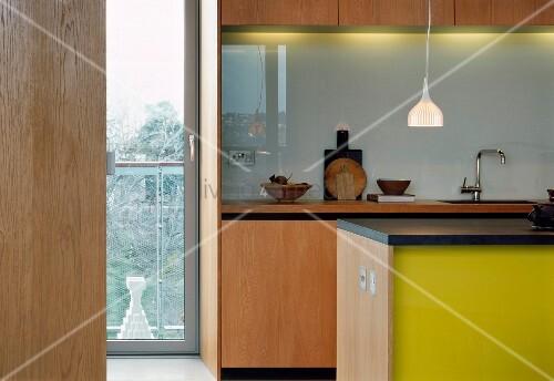 blick durch offene t r in moderne k che mit theke und gelb lackierter front bild kaufen. Black Bedroom Furniture Sets. Home Design Ideas