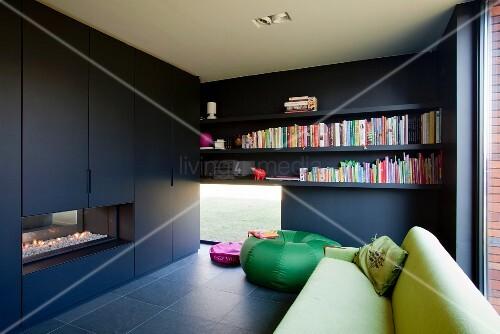 Schwarzer Einbauschrank mit integriertem Kamin vor grünes Sofa