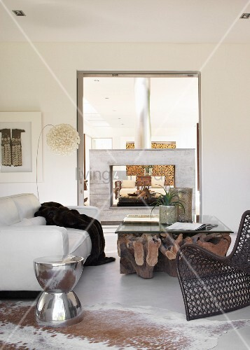 View through adjoining rooms with frame-shaped, free-standing fireplace - glass top on huge, gnarled tree stump and stainless steel, drum-shaped side table