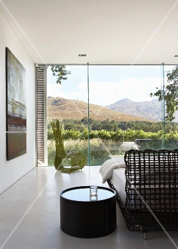Bedroom with amazing view of landscape through frameless glass wall - round night stand next to delicate latticed bed frame
