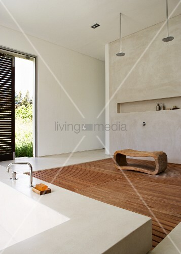 Unusual bathroom with access to garden - artistic wooden stool on wooden slatted floor in front of narrow, horizontal niche with modern bathtub in foreground