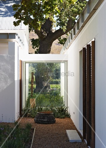 Glass walkway between two buildings of a contemporary home, Courtyard with flagstone in the gravel path serving as a doorstep.