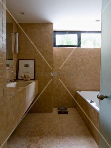 Modernes Bad Mit Sandfarbenen Fliesen   Waschtisch Und Badewanne Mit  Gleichen Fliesen Belegt Wie Wand Und Boden
