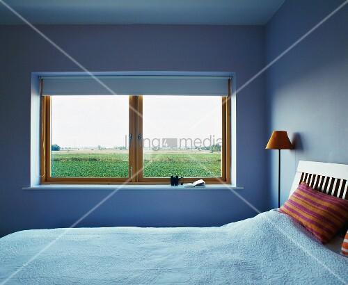 schlichter schlafraum in hellblau und fenster mit ausblick bild kaufen living4media. Black Bedroom Furniture Sets. Home Design Ideas