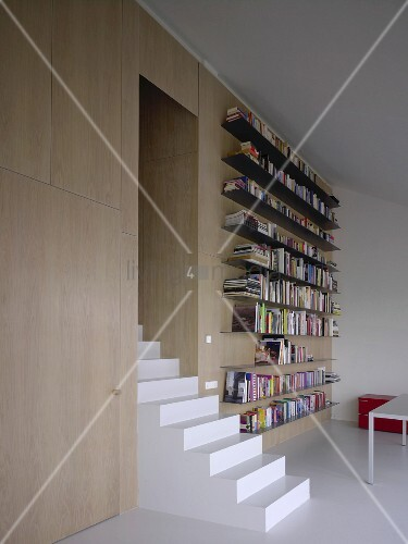 Moderner Seminarraum - Treppe aus einem Block vor langen Bücherboarden aus Metall an holzverkleideter Wand