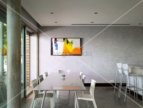Colourful painting in grey room - long metal dining table and white plastic chairs next to kitchen counter with bar stools