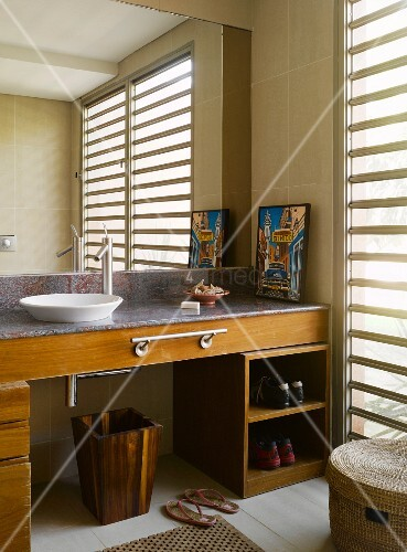 Large bathroom mirror over sink on wood and stone washstand with towel rail and shoe rack