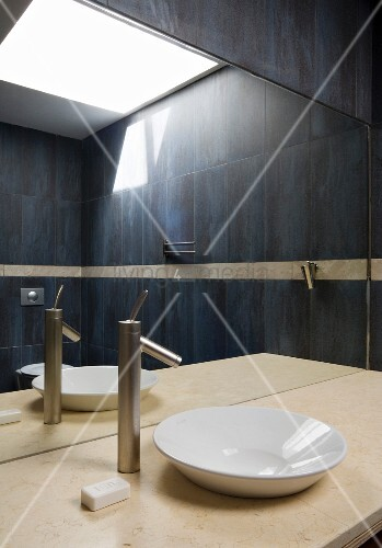 Dark tiled bathroom with skylight in mirror above marble top with basin and modern tap fitting