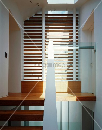 lamellen vor raumhohem fenster und treppenstufen aus holz im modernen treppenhaus bild kaufen. Black Bedroom Furniture Sets. Home Design Ideas