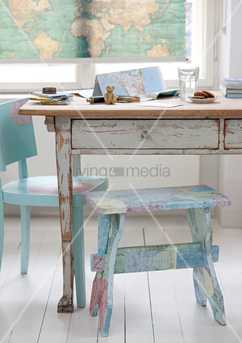 Kitchen table with flaking paint and painted footstool on white wood floor