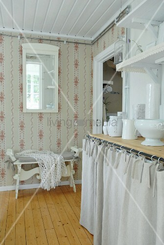 Country-style kitchen with patterned wallpaper and white crockery on kitchen counter with curtained front below wall brackets with lace trim