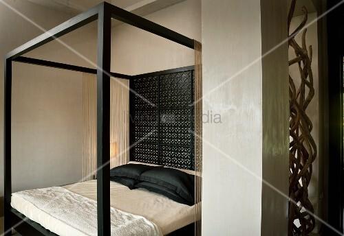 modernes himmelbett mit schwarzem rahmen und r ckwand aus feinem holzornament in elegantem. Black Bedroom Furniture Sets. Home Design Ideas