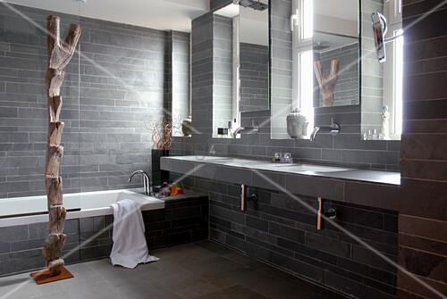 Graues badezimmer mit steinfliesen am boden und an den wänden und
