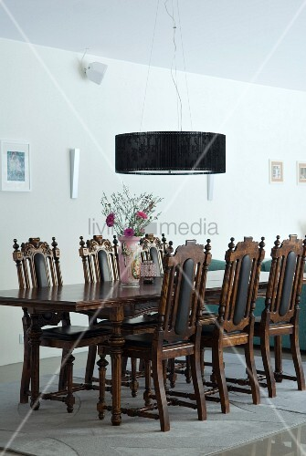 English-style dining table and chairs below modern pendant lamp in dining room