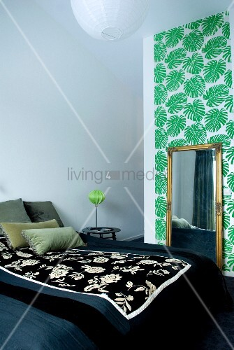 A large double bed with a floral quilt and an antique mirror in front of a a wall decorated with palm leaf patterned wallpaper