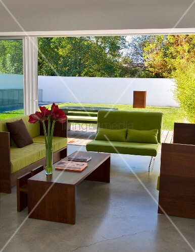 Sofa with lime green cushions and wooden frame and matching coffee table in front of floor-to-ceiling terrace windows in contemporary building
